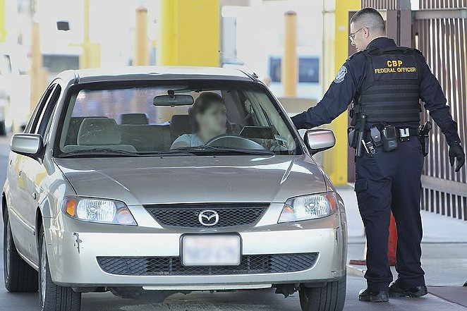 A border patrol officer checks a car crossing into the United States. - U.S. CUSTOMS AND BORDER PROTECTION