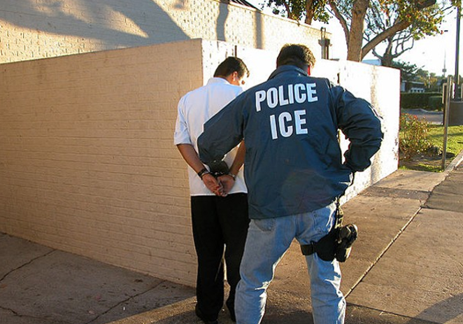 An ICE agent detains a suspect. - WIKIMEDIA COMMONS
