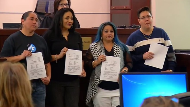 The women known as the San Antonio Four show off the papers expunging their criminal histories. - VIA @NEWS4SA
