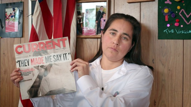 A still from the documentary film Southwest of Salem of Anna Vasquez holding a 2012 issue of the San Antonio Current featuring a cover story about the case of the San Antonio Four. - MOTTO PICTURES AND NAKED EDGE FILMS