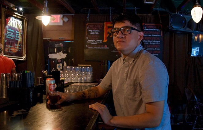 Sous chef JC Rodriguez enjoys a drink inside the cool and dark confines of Faust, his favorite local watering hole. - LEA THOMPSON