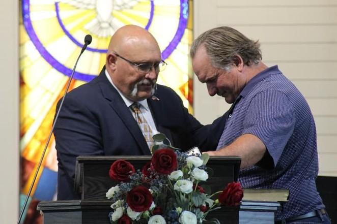 Frank Pomeroy (left) prays with a congregant. - TWITTER / @KERANEWS