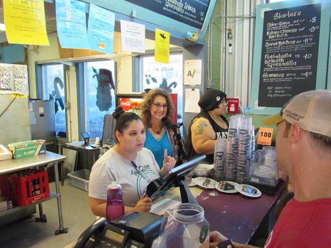 Lisa Asvestas smiles as an employee helps a customer. - SANFORD NOWLIN
