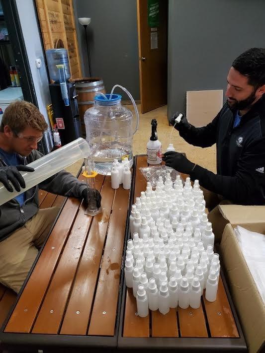 Ranger Creek employees mix up hand sanitizer to package in spray bottles. - COURTESY PHOTO / RANGER CREEK