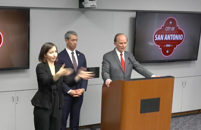 Bexar County Judge Nelson Wolff addresses the press while a sign language interpreter translates. - SCREEN CAPTURE / TVSA