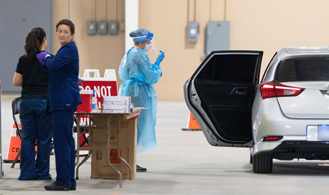 Healthcare workers assist with a drive-through coronavirus test at San Antonio's Freeman Coliseum site. - COURTESY PHOTO / CITY OF SAN ANTONIO