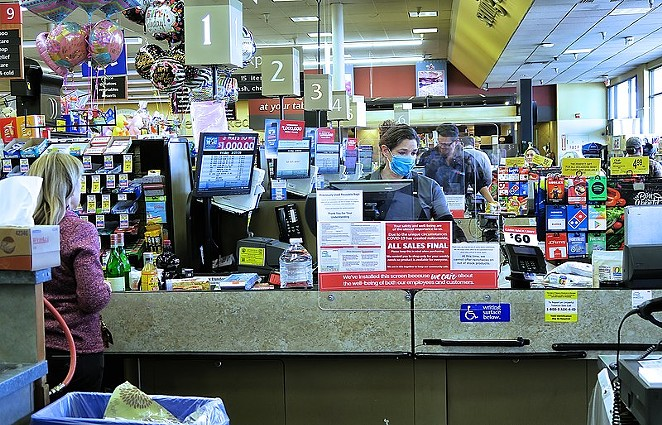 A grocery store checker works in her mask and behind a protective shield. - RUSS ALLISON LOAR / WIKIMEDIA COMMONS