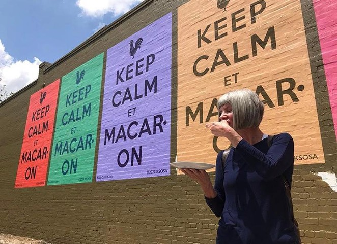 Kathy Sosa eats a macaron in front of the new mural. - TWITTER / SOUTHWEST SCHOOL OF ARRT