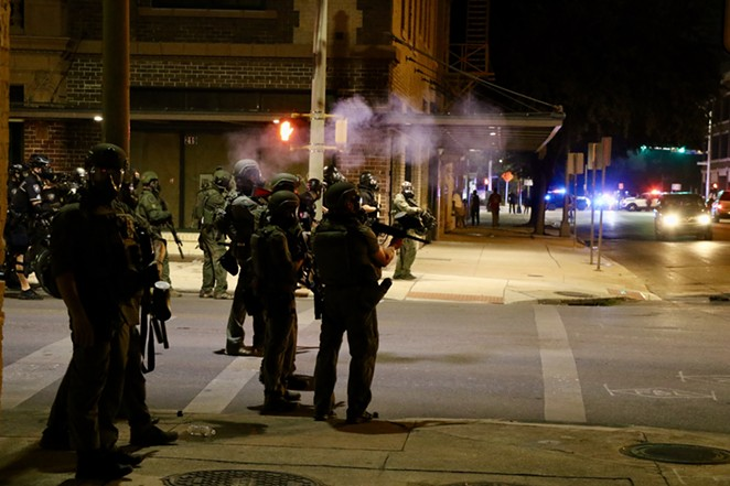 Police in riot gear stand on a downtown street corner. - JAMES DOBBINS