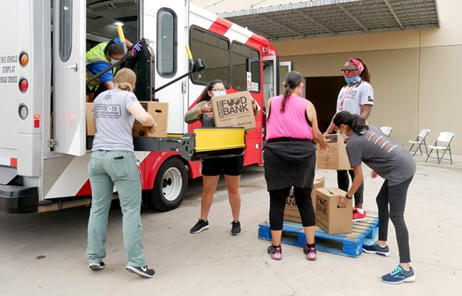 Volunteers load a bus with food on June 26.