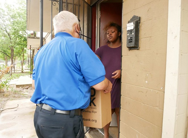 Janece Johnson, who lives at Alazan-Apache Courts, receives a box of food on June 26.