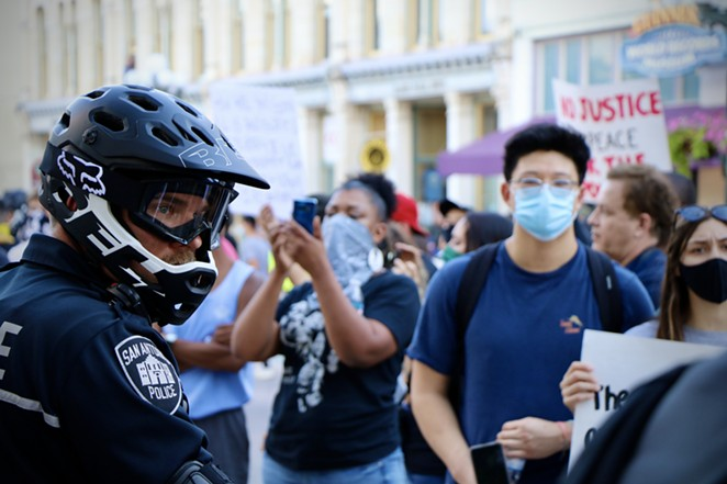 Protesters march by a San Antonio police officer at a demonstration this spring. - JAMES DOBBINS