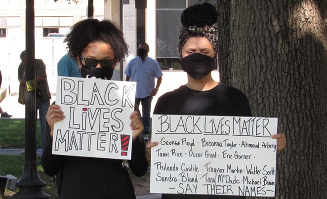 Two protesters hold up signs at a San Antonio march against police brutality. - SANFORD NOWLIN