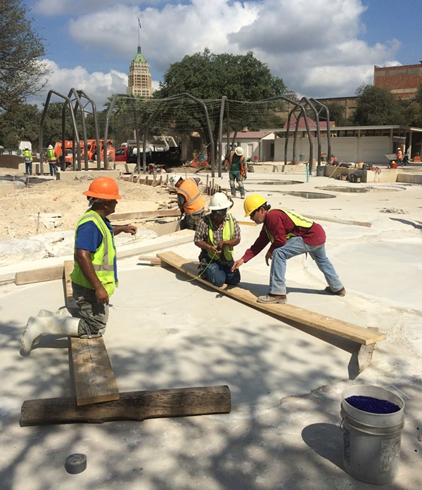 Oscar Alvarado works with construction crew members to create an undulating ripple effect in concrete. - BRYAN RINDFUSS