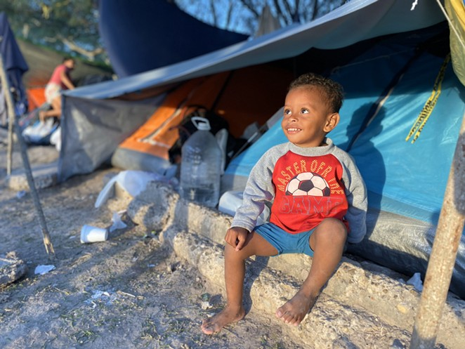 """A child waits in a shelter at a Matamoros border camp. Trump's """"remain in Mexico"""" policy has faced criticism for exposing asylum seekers to violence and unsanitary conditions in encampments along the border. - TWITTER / @CLARAB_KGBT"""