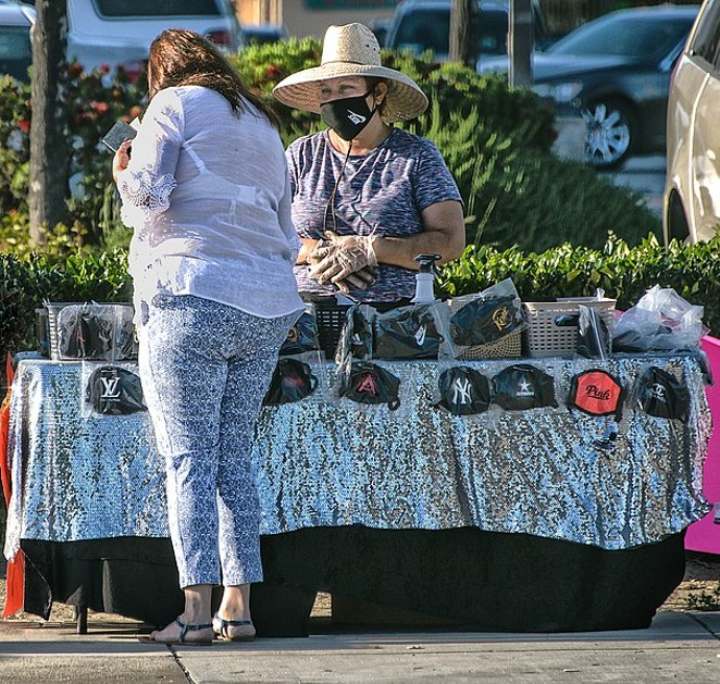 A woman shops for face masks with a sidewalk vendor. - WIKIMEDIA COMMONS / RUSS ALLISON LOAR