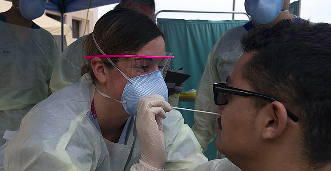 A medical technician swabs a patient at a COVID-19 testing site. - WIKIMEDIA COMMONS / U.S. NAVY