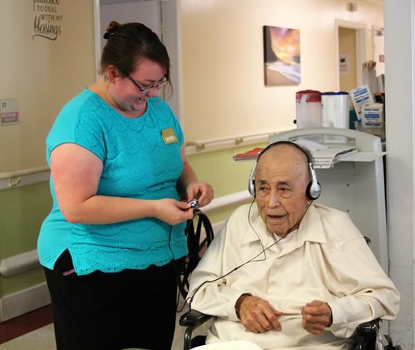 Stonebrook Manor's Activity Assistant helps Mr. Gallegos listen to his favorite, conjunto. - TIM SLUSHER