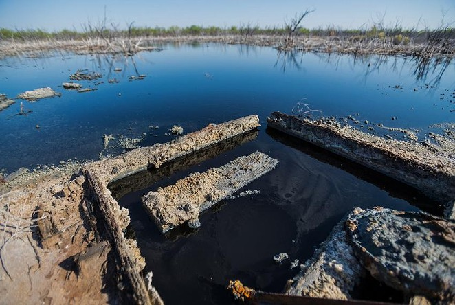 """Brackish water flows from an unplugged abandoned well outside of Imperial in Pecos County. Texas reported more than 6,000 documented """"orphan"""" oil wells in 2019, almost all on private land, but some experts believe that's an underestimate. - TEXAS TRIBUNE / RAFAEL AGUILERA"""