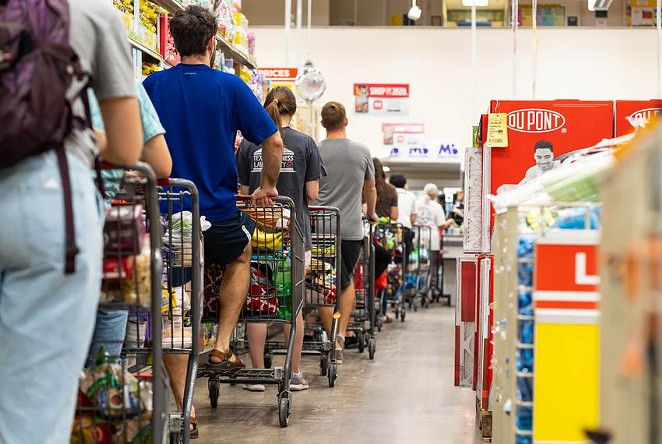 Grocery shoppers formed a long line at the H-E-B grocery store at Hancock Center in Austin last year. Grocery store employees were called essential when the pandemic began, but haven't been given priority access to the coronavirus vaccine. - TEXAS TRIBUNE / JORDAN VONDERHAAR