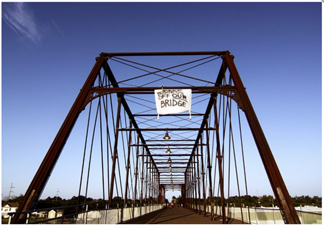 Activists climbed the Hays Street Bridge to hang a banner opposing development after plans for a brewery on public land emerged in 2012. - MICHAEL BARAJAS