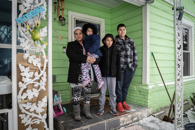 Marleny Almendarez, 38, with her niece Madelyne Hernandez, 3, and two boys, Aaron Hall, 11, and Matthew Hall, 14, outside their home in Dallas on Feb. 18, 2021. The family spent two nights at a mobile warming station to avoid the cold temperatures. - BEN TORRES FOR THE TEXAS TRIBUNE