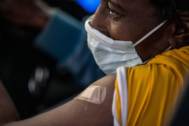 Necole Williams has a band-aid covering her injection site at a 24-hour vaccination event at Kelly Reeves Athletic Complex on March 6, 2021, in Austin. Family Hospital Systems hosted the drive-thru vaccine event with an 80s theme and equipped to vaccinate 7,000 people. - TEXAS TRIBUNE / SERGIO FLORES