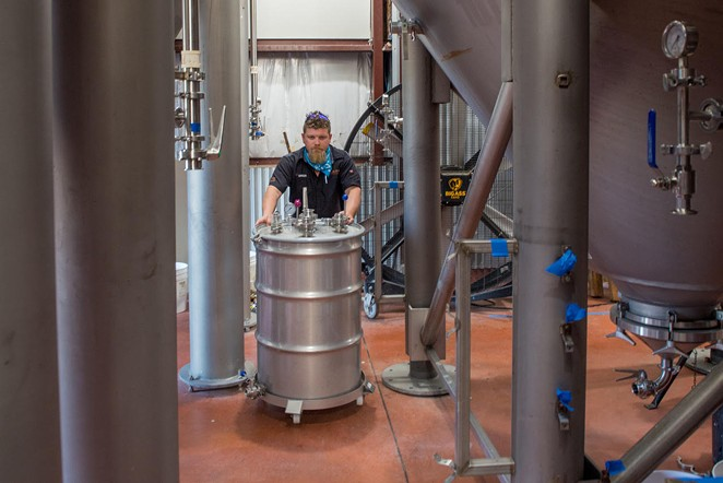 Head brewer Gregg Spickler moves fermentation tanks which yield CO2 naturally as a byproduct of beer making. - COURTESY OF ALAMO BEER CO.