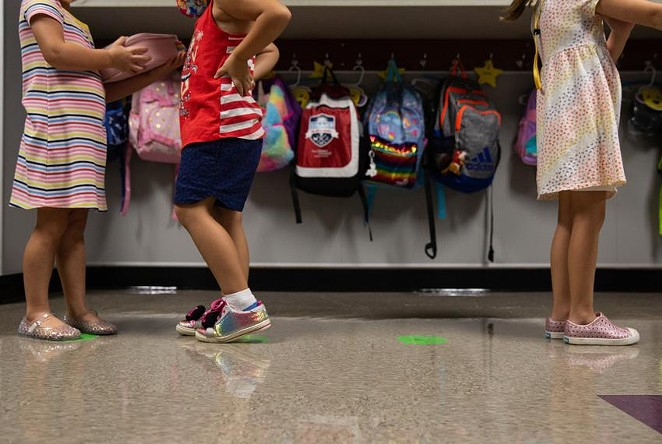 Kindergarten students line up on social distancing markers on the first day of in-person classes at Highland Village Elementary last year. - TEXAS TRIBUNE / SHELBY TAUBER
