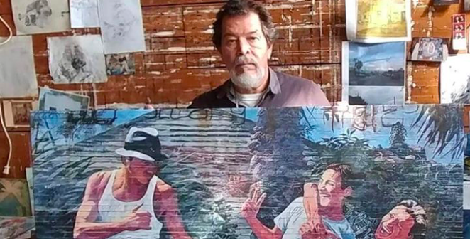 Adan Hernanez holds up one of his paintings in a photo shared on a GoFundMe account set up to cover his funeral expanses. - GOFUNDME / ARMANDO HERNANDEZ