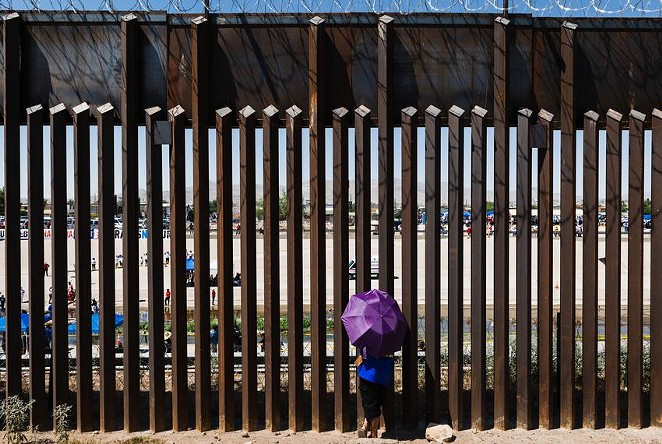 A woman looks through the border wall towards her family in Ciudad Juarez, Mexico from El Paso, Texas on June 19, 2021. - JUSTIN HAMEL / THE TEXAS TRIBUNE