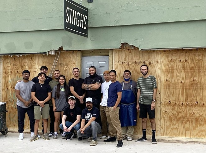 Employees of Singh's Vietnamese pose in front of the restaurant's now boarded-up storefront. - INSTAGRAM / SINGHS_SA