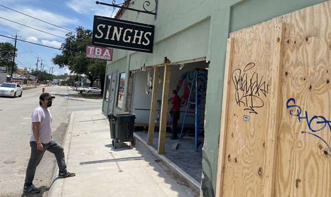 Eric Treviño, a partner in Singhs, watches a work crew clear debris out from the restaurant after it was struck by a car last weekend. - SANFORD NOWLIN