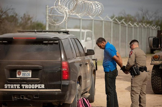 A Texas Department of Public Safety trooper arrests Nerio, a Venezuelan migrant, on private riverside property in Del Rio, just beyond a newly installed fence paid for by the state. Credit: Miguel Gutierrez Jr./The Texas Tribune - TEXAS TRIBUNE / MIGUEL GUTIERREZ JR.
