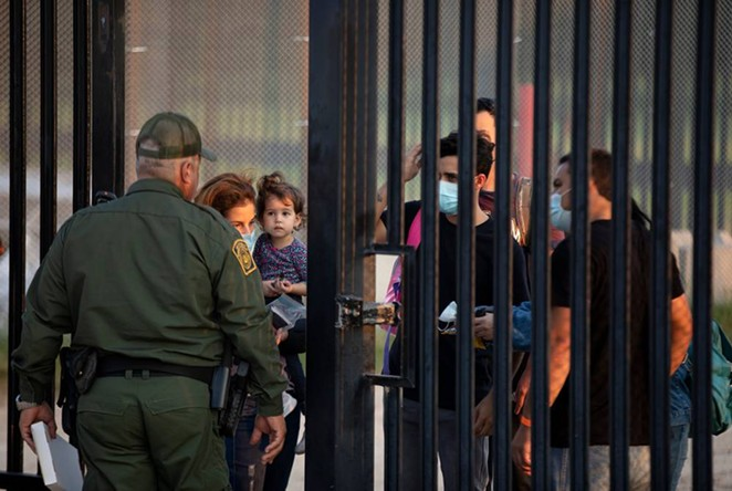 A group of migrants wait to turn themselves over to National Guard and Customs and Border Patrol officials at the U.S. and Mexico border in Del Rio on July 22, 2021. - TEXAS TRIBUNE / MIGUEL GUTIERREZ JR.