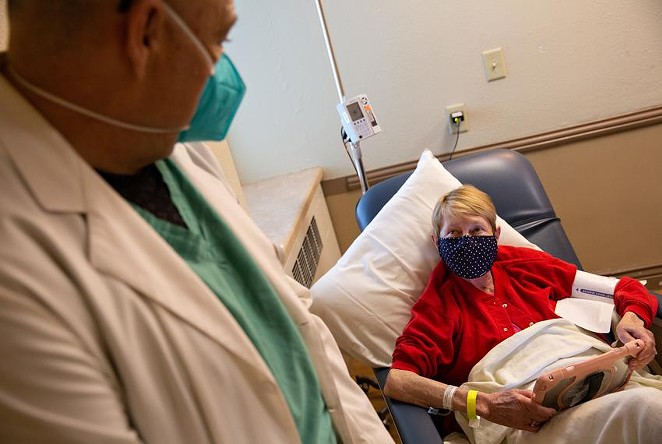 Dr. Fritz Thurmond speaks to Kathy Hardman during a one-hour observation period after receiving a COVID-19 antibody infusion Aug. 19 at Titus Regional Medical Center in Mount Pleasant. - TEXAS TRIBUNE / SHELBY TAUBER