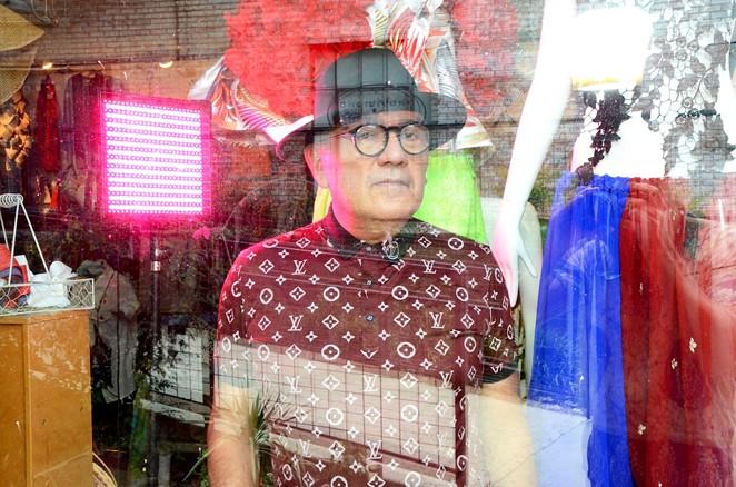 San Antonio designer Agosto Cuellar in the window of his new Blue Star boutique Augustine. - BRYAN RINDFUSS