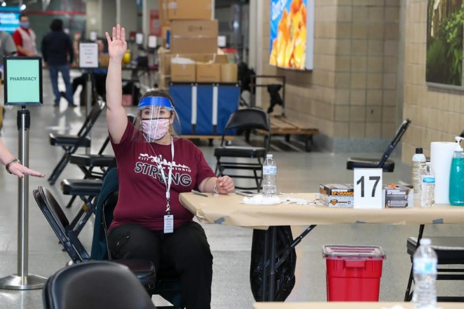 A worker at the City of San Antonio's Alamodome vaccination site calls on the next person in line to get their shot. - COURTESY PHOTO / CITY OF SAN ANTONIO