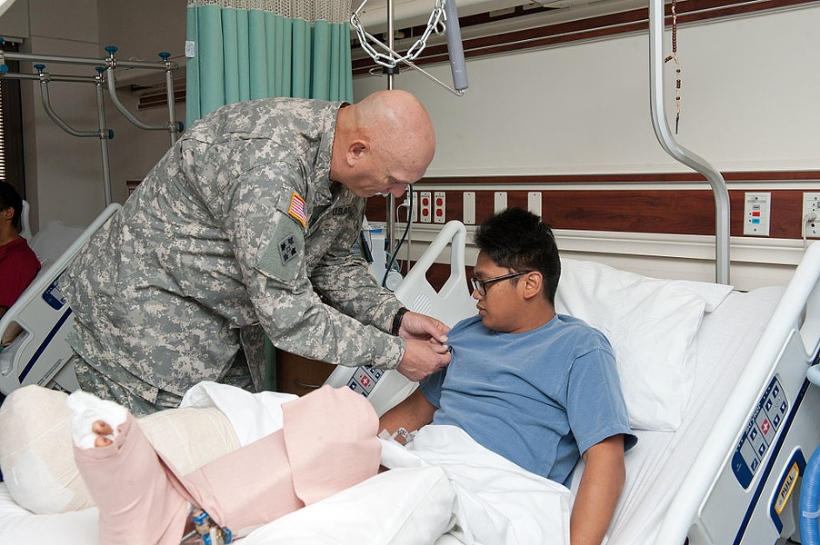 U.S. Army Chief of Staff Gen. Raymond T. Odierno pins a Purple Heart Medal on a wounded soldier at Brooke Army Medical Center in this 2011 image. - WIKIMEDIA COMMONS / STAFF SGT. TEDDY WADE