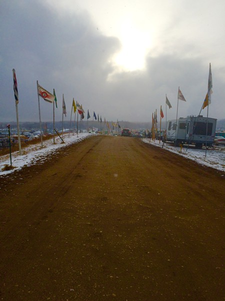 Local protesters will plant a Cruz Ortiz-designed banner next to these flags lining the main road to the Standing Rock protest camps. - COURTESY JENNIFER FALCON