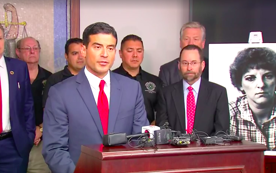 Distract Attorney Nico LaHood addresses reporters on Friday, with a dated photo of Genene Jones behind him. - SCREENSHOT, NEWS 4 VIA FACEBOOK
