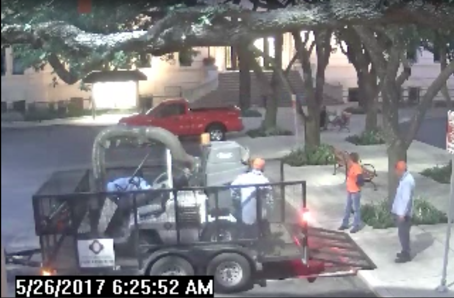 City landscapers watch as a security guard wakes Councilman Alan Warrick - CITY OF SAN ANTONIO VIA SAN ANTONIO EXPRESS-NEWS