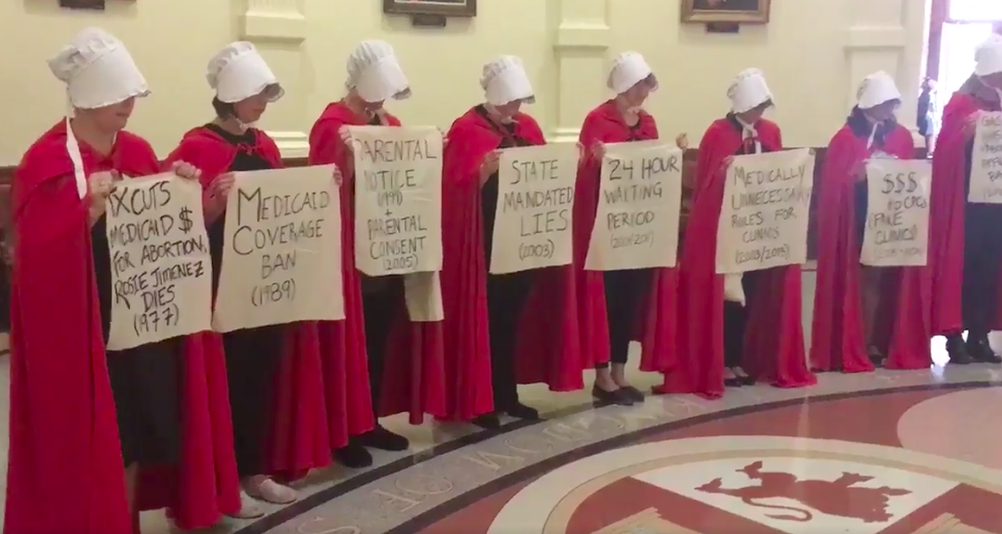 Women dressed like characters from The Handmaid's Tale protesting anti-abortion bills at the Texas state capitol. - SCREENSHOT, ALEXA GARCIA-DITTA VIA TWITTER.COM