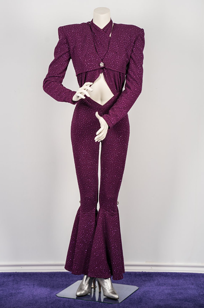 """This iconic jumpsuit was personally designed by Selena in her favorite color, purple. It was worn during her last major concert in the Houston Astrodome on February 26, 1995. The purple jumpsuit features bell bottoms and rhinestone broches at the side of both knees and at the front of the removable jacket."""