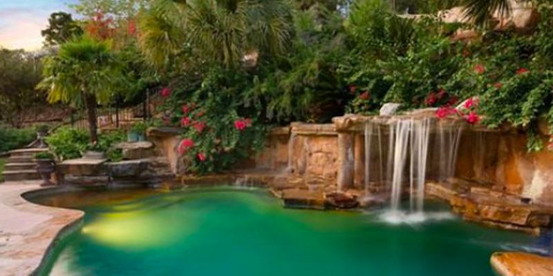 The waterfall-fed pool of this $1.9 million San Antonio mansion looks like a tropical lagoon