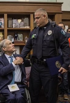 Greg Abbott shakes the hand of a participant in his school safety roundtable.
