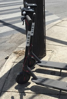 A pair of dockless scooters sit on a sidewalk along North St. Mary's Street.