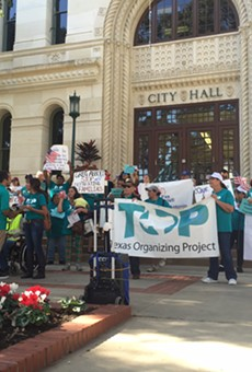Members of the Texas Organizing Project rally outside of city hall.