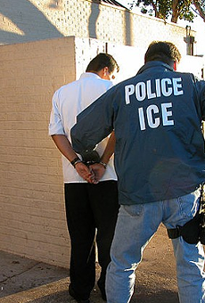 An ICE agent detains a suspect.
