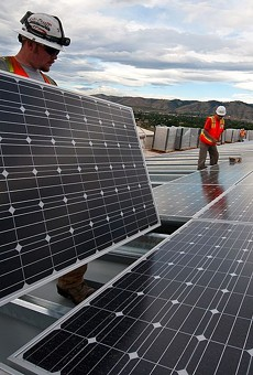 Workers conduct a solar panel installation project.